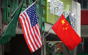 The US (L) and Chinese flags are displayed outside a hotel in Beijing on May 14, 2019. - Beijing's latest retaliation against US tariff hikes -- an increase on $60 billion of US imports from June 1 -- could leave China running low on ammunition in the trade war. (Photo by Greg Baker / AFP)