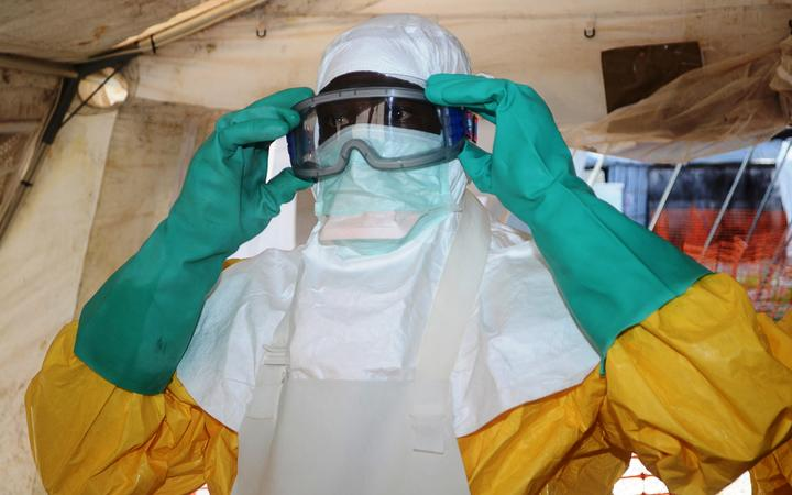 A member of Doctors Without Borders (MSF) putting on protective gear at Donka Hospital in Conakry, where people infected with the Ebola virus are being treated in June, 2014.