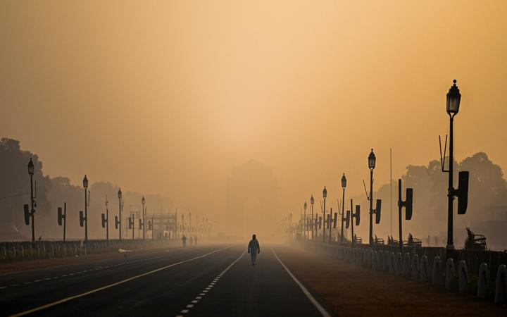 A man walks along Rajpath amid smoggy conditions in New Delhi on January 28, 2021.