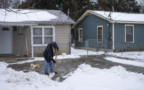 A Waco, Texas, resident clears snow from his driveway on 17 February 2021.