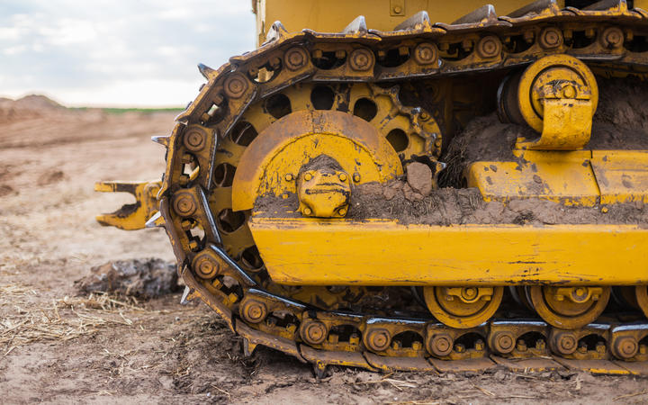 Yellow Tractor on caterpillar tracks, tractor tracks