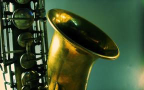 Artistic shot of a tenor saxophone on a blue-green background