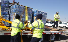 Workers with Houston Public Works unload pallets of water from a truck during a mass water distribution at Delmar Stadium on February 19, 2021 in Houston, Texas. and precipitation. Many Houston residents do not have drinkable water at their homes and are relying on city water giveaways.