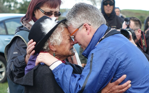 New Plymouth mayor Andrew Judd is embraced by Parihaka elder Te Whero o te Rangi Bailey after the peace hiko entered Parihaka.