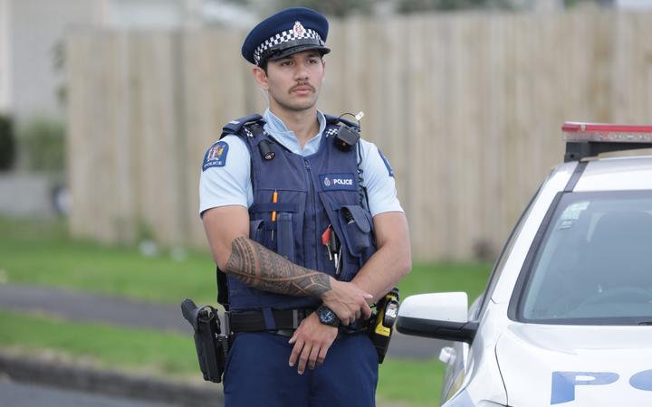 A police officer standing guard at a cordon in Papatoetoe after a man was shot by police.