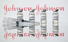A file photo taken on November 17, 2020 shows vials with Covid-19 Vaccine stickers attached and syringes with the logo of US pharmaceutical company Johnson & Johnson in London.
