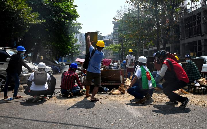 Protesters take cover behind makeshift barricades, made to obstruct security forces, during a demonstration against the military coup in Yangon on 28 February