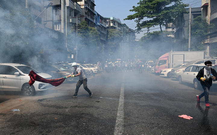 Protesters run after police fired tear gas to disperse them during a demonstration against the military coup in Yangon on 28 February