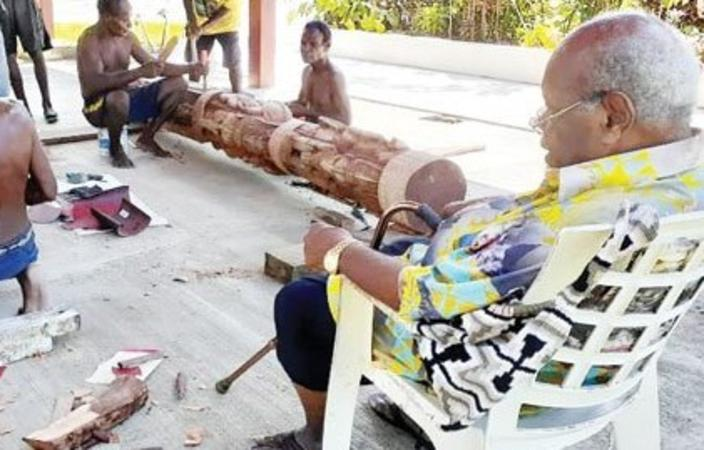 Sir Michael Somare, right, watches the carvers work on his 'special gift'.