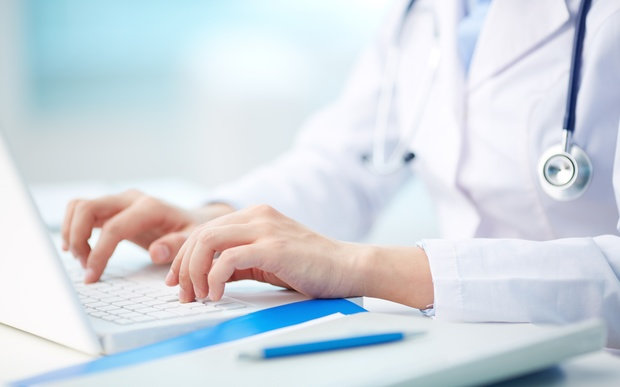 An image of a doctor typing on a laptop
