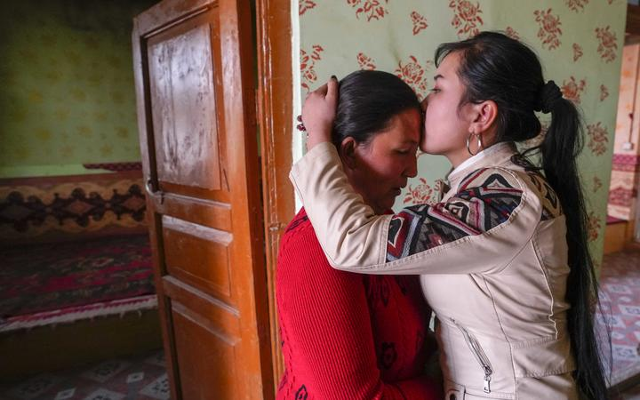 Buzeynep Abulehet,the eldest daughter of a family of six, kisses her mother before leaving for work, at her home in Moyu of Hotan Prefecture, northwest China's Xinjiang Uygur Autonomous Region, March 26, 2020.
