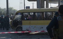 Afghan policemen look at the site of a suicide attack to have hit a minibus carrying foreign security guards in Kabul.