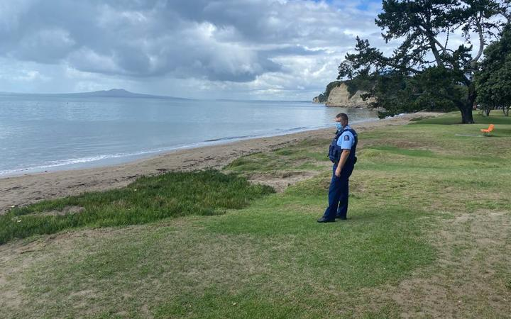 Police patrol a deserted Browns Bay in Auckland's North Shore.
