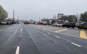 A line of law enforcement cars block the area of a shooting at a spa in an Atlanta suburb.