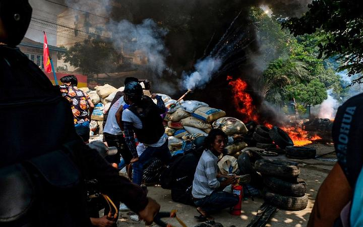 Smoke rises after protesters burn tyres as they gather to continue their protest against military coup.