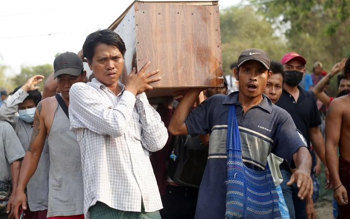 Mourners carry the coffin of Tin Hla, 43, who was shot dead by security forces during a protest against the military coup in Thanlyin township, outskirts of Yangon, Myanmar on March 27, 2021.