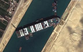 Tug boats and dredgers on March 27, 2021, attempting to free the ship Ever Given, which was lodged sideways and impeding all traffic across Egypt's Suez Canal.