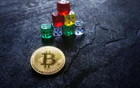 Gold bitcoin and stacked dice -- cryptocurrency investing and risk concept