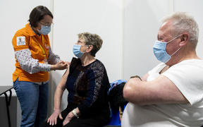 A caregiver giving an intramuscular injection of PFIZER vaccine during a mass vaccination campaign at gayant expo in Douai in France.