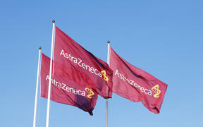 Three purple flags with the logo for Atrazeneca flying in the wind on top of the flagpoles against the blue sky.