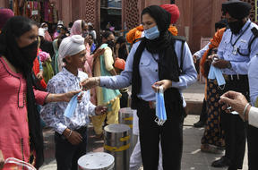 Private security guards distribute facemasks to people during an awareness campaign against the spread of the Covid-19 coronavirus, in Amritsar on 4 April 2021.
