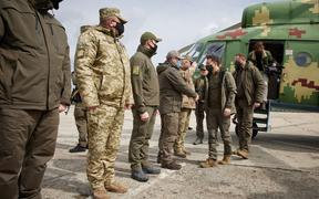 Ukrainian President Volodymyr Zelensky  shakes hands with soldiers during his visit to a front in Donbass, Ukraine.