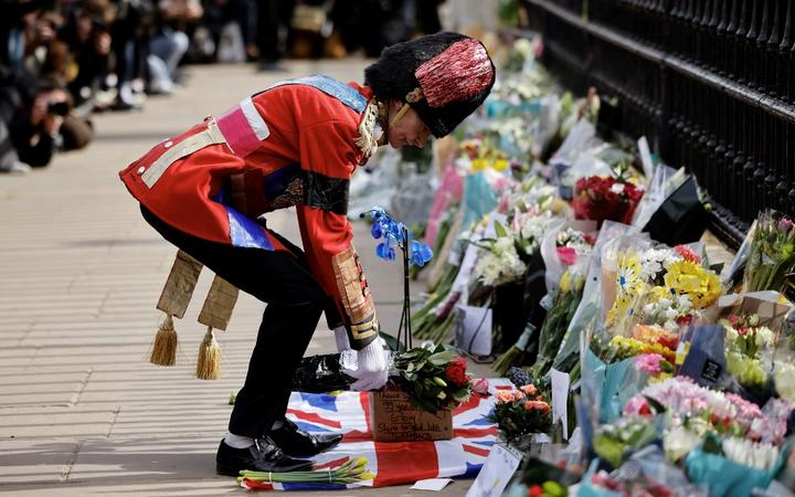 An ardent Royals fan lays a floral tribute at the front of Buckingham Palace in central London on April 9, 2021 after the announcement of the death of Britain's Prince Philip, Duke of Edinburgh.