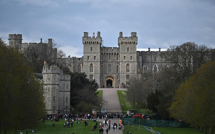 People walk through Windsor Great Park along the Long Walk with Windsor Castle in the background, in Windsor, west of London, on April 9, 2021, following the announcement of the death of Britain's Prince Philip, Duke of Edinburgh.