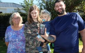 Isaac McCallum has an app on his cellphone so if he wanders off in a semi-conscious state before a seizure, family (from left) his mother Teresa and partner Abbie Willoughby, holding son Harrison, will be able to call police who can track his location.