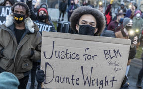"A protester holds a sign reading ""Justice for Daunte Wright"" during a rally outside the Brooklyn Center police station to protest the death of Daunte Wright who was shot and killed by a police officer in Brooklyn Center, Minnesota on 13 April 2021."