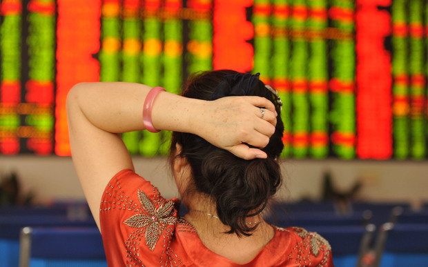 A concerned Chinese investor looks at prices of shares (red for price rising and green for price falling) at a stock brokerage house in Fuyang city, east China's Anhui province, 24 June 2016.