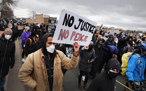 Demonstrators protesting the shooting death of Daunte Wright march to the FBI offices from the Brooklyn Center police station on 13 April 2021 in Brooklyn Center, Minnesota.
