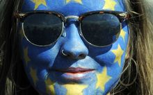 A festival-goer with a European flag painted on her face poses for a photograph on day three of the Glastonbury Festival.