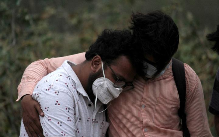 A man is consoled by his relative during the burial of his father, who died of coronavirus (Covid-19), at a graveyard in New Delhi on April 16, 2021.