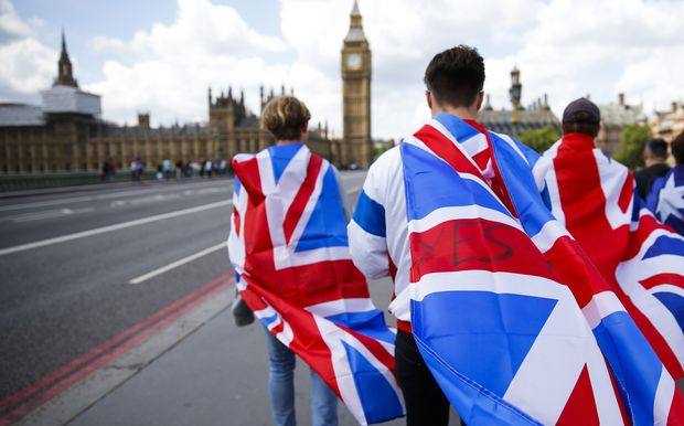 People walk over Westminster Bridge wrapped in Union flags.