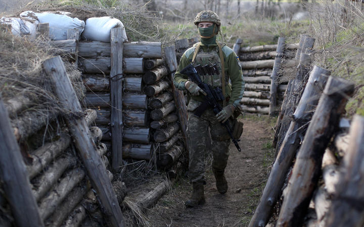 A Ukrainian serviceman patrols along a trench in Schastya, Lugansk region, near the frontline with Russia-backed separatists yesterday.