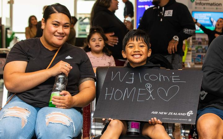 A boy holds a 'welcome home' sign as families wait for people on board the first flight from Sydney to Auckland under the trans-Tasman bubble arrangement.