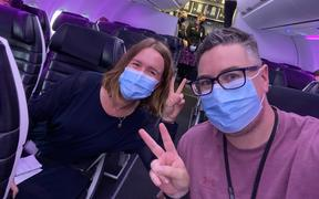 RNZ journalist Tess Brunton and videographer Simon Rogers on board the first flight from Auckland to Sydney after the trans-Tasman bubble opened.