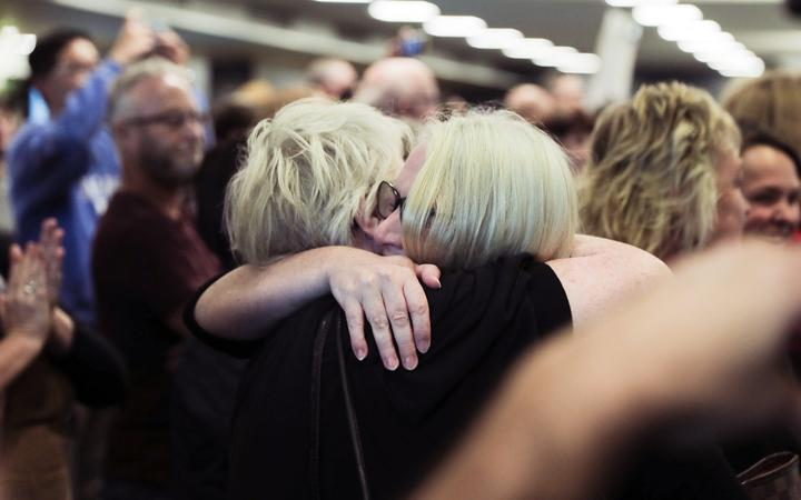 A passenger is reunited with loved ones after the first quarantine-free Wellington flight from Auckland disembarks.