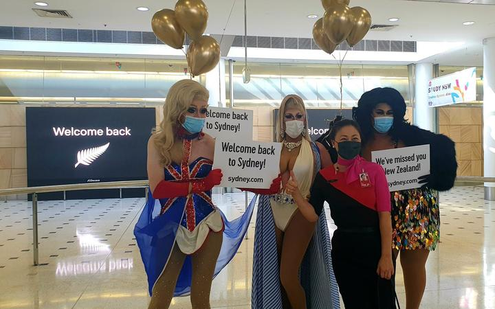 Drag queens welcome visitors to Australia on the first day of the trans-Tasman bubble