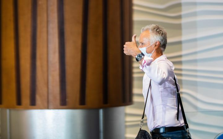 A passenger gives a thumbs-up as he walks into the arrivals hall after flying from Sydney to Auckland Airport.