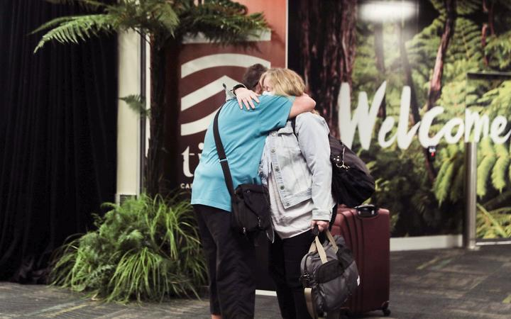 A passenger is reunited with loved ones after the first quarantine-free Wellington flight from Australia disembarks.