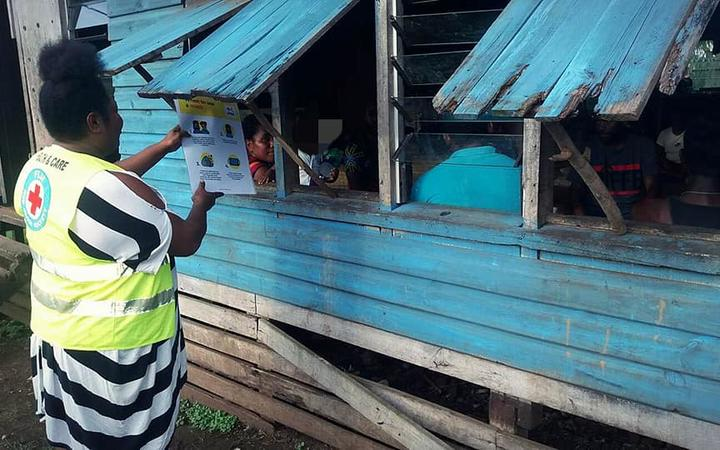 A Red Cross volunteer shares a message about Covid-19 transmissions through a window to a family in Uciwai Settlement, Nadi.