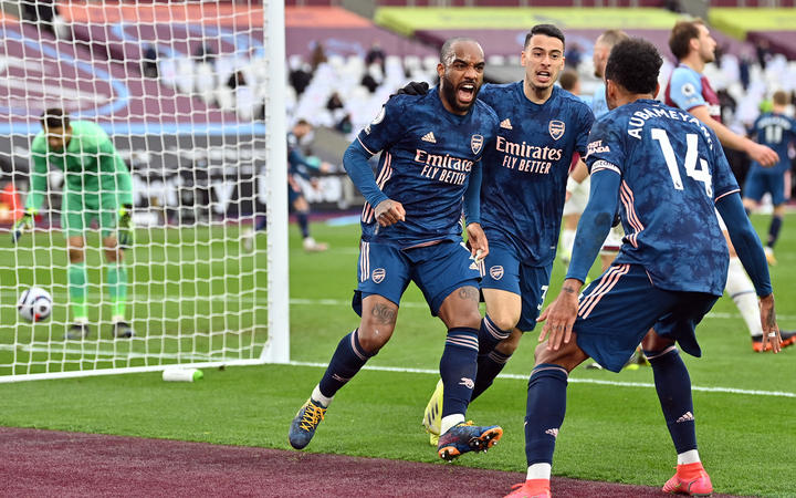 Arsenal's French striker Alexandre Lacazette, left, celebrates scoring his team's third goal during the English Premier League football match between West Ham United and Arsenal at The London Stadium, in east London on March 21, 2021.