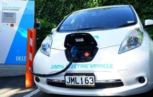 An a white electric car with a black cable running into the bonnet at a charging station, Dunedin