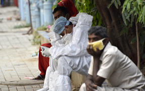 A health worker wearing a PPE Kit, rests on a foothpath of a government hospital during coronavirus emergency in Kolkata, India.