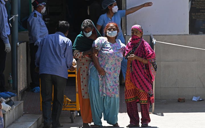 A Covid-19 coronavirus patient is helped by her relatives as she leaves a hospital in New Delhi on April 24.