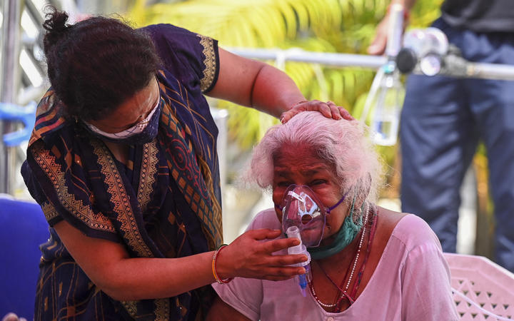 A Covid-19 patient breathes with the help of oxygen provided by a Gurdwara, a place of worship for Sikhs, under a tent installed along a roadside in Ghaziabad on 28 April 2021.