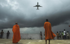 Buddhists monks and children look out from the rooftop at a Buddhist mission hostel and school for underprivileged children as an international passenger flight takes off from Kolkata, India.