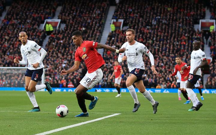 Marcus Rashford of Manchester United is surrounded by Liverpool defenders.